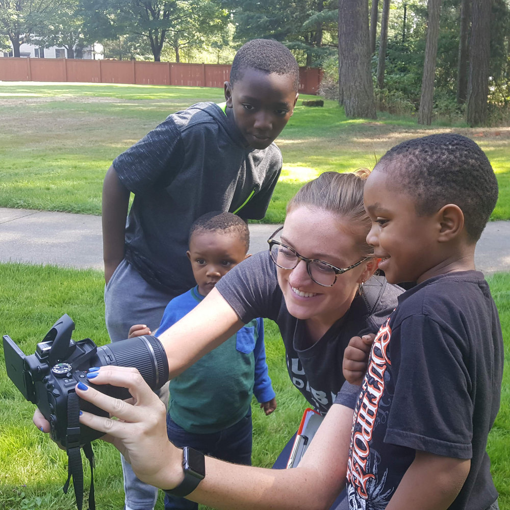 girl holding camera with three boys