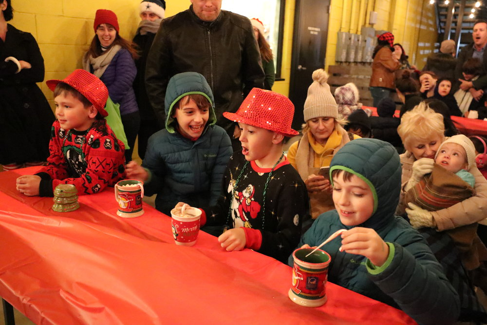 Kiddos gathered round with hot cocoa, ready to sing along (or giggle instead).