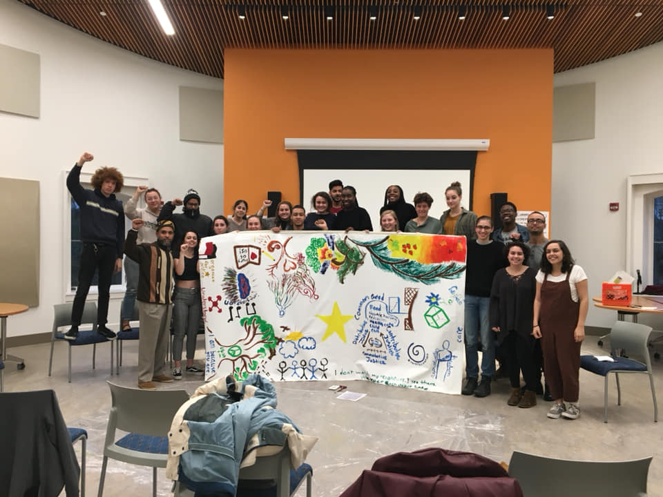 Students posing together with the mural they created.