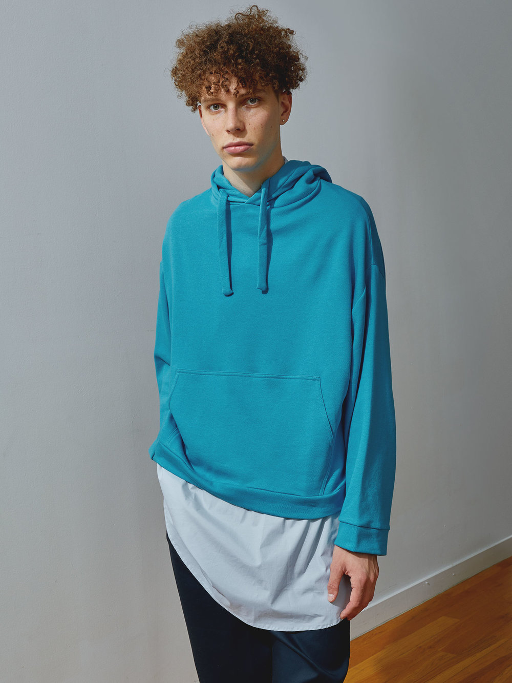 Jean Wears Turquoise Gender-neutral Hoodie by One DNA