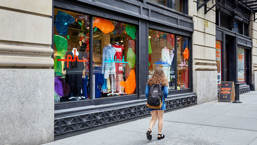 A passerby browses the windows at The Phluid Project in NYC.