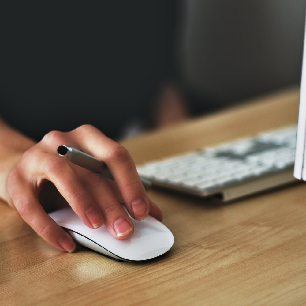 A person's hand on a computer mouse