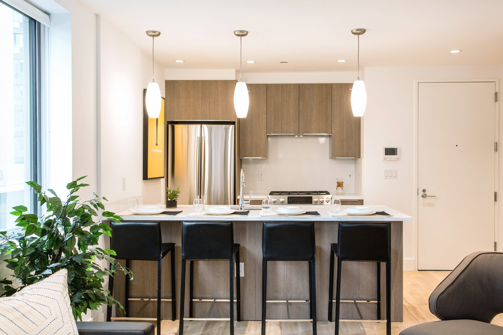 THE KITCHENS - The thoughtfully designed kitchens pair wood cabinetry and Caesarstone countertops with Samsung refrigerators, Bosch gas ranges and dishwashers.