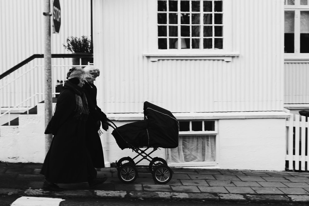 Two woman push infant against wind