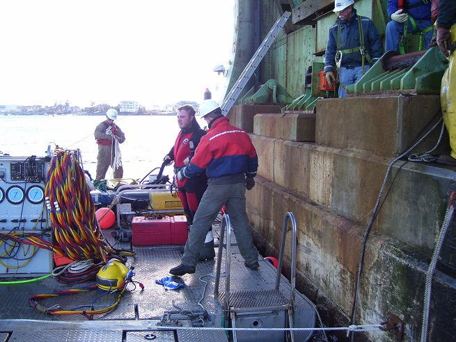 Diver dressing in while Cianbro's surface team readies for first cable pull