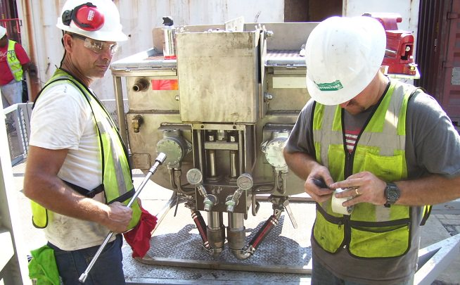 Technicians maintenance patented epoxy pump at port facility