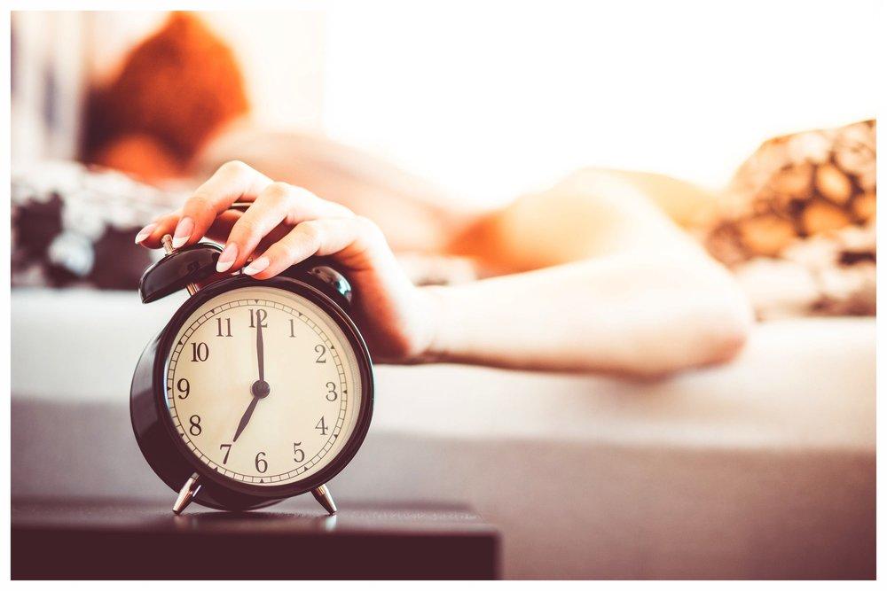 woman-shutting-off-ringing-alarm-clock-from-bed-picjumbo-com.jpg