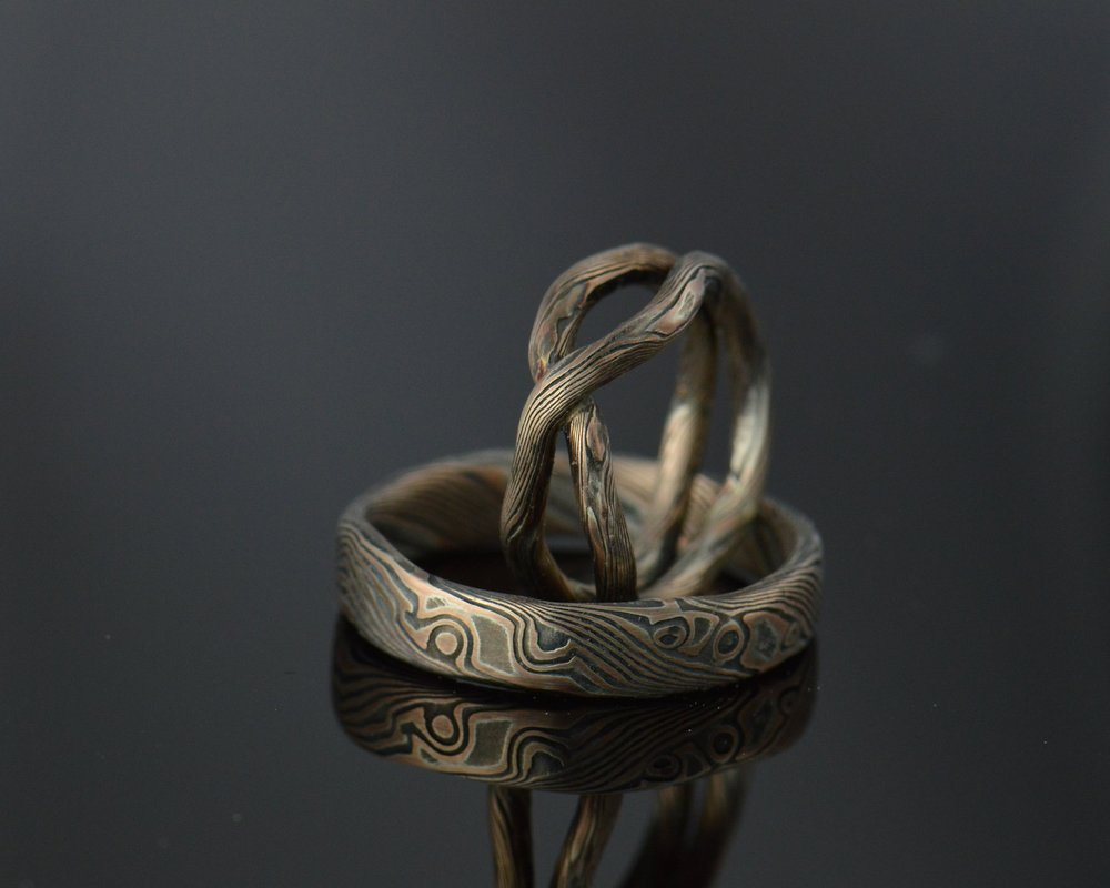 Perhaps you create a hand forged wedding band set with a dark noir patina over 14k rose gold.