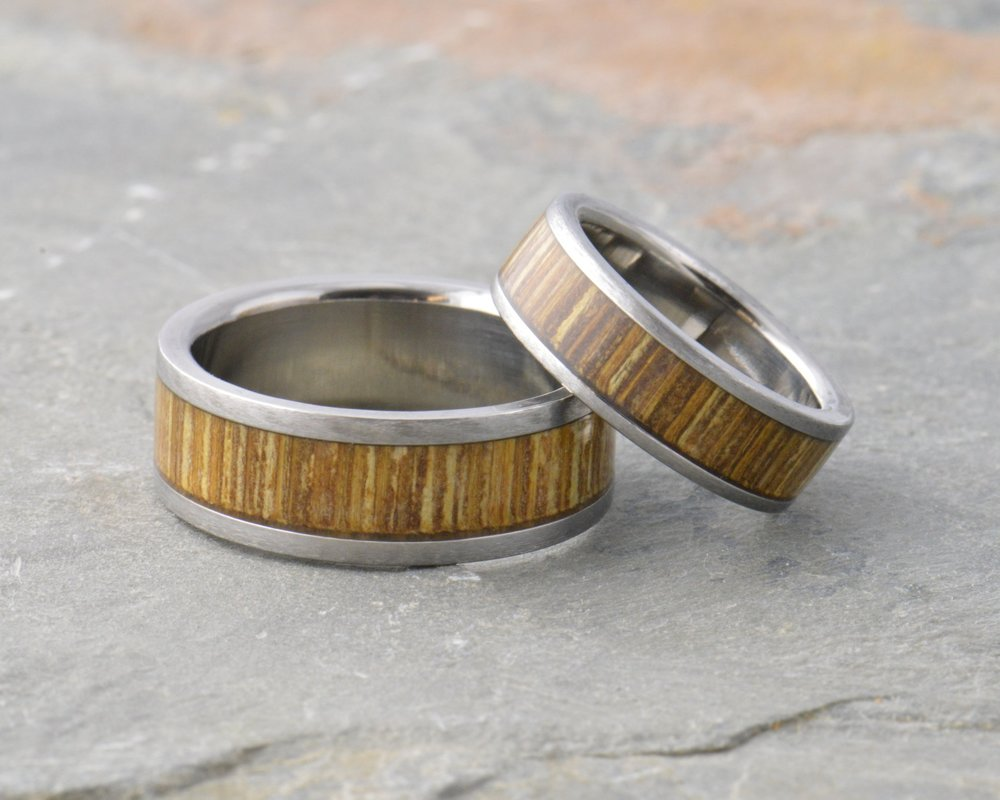 Wood inlays - A single piece of wood, turned on a lathe and placed in titanium or stainless rings under a durable acrylic sealant. We offer many hardwood and design options, just ask.