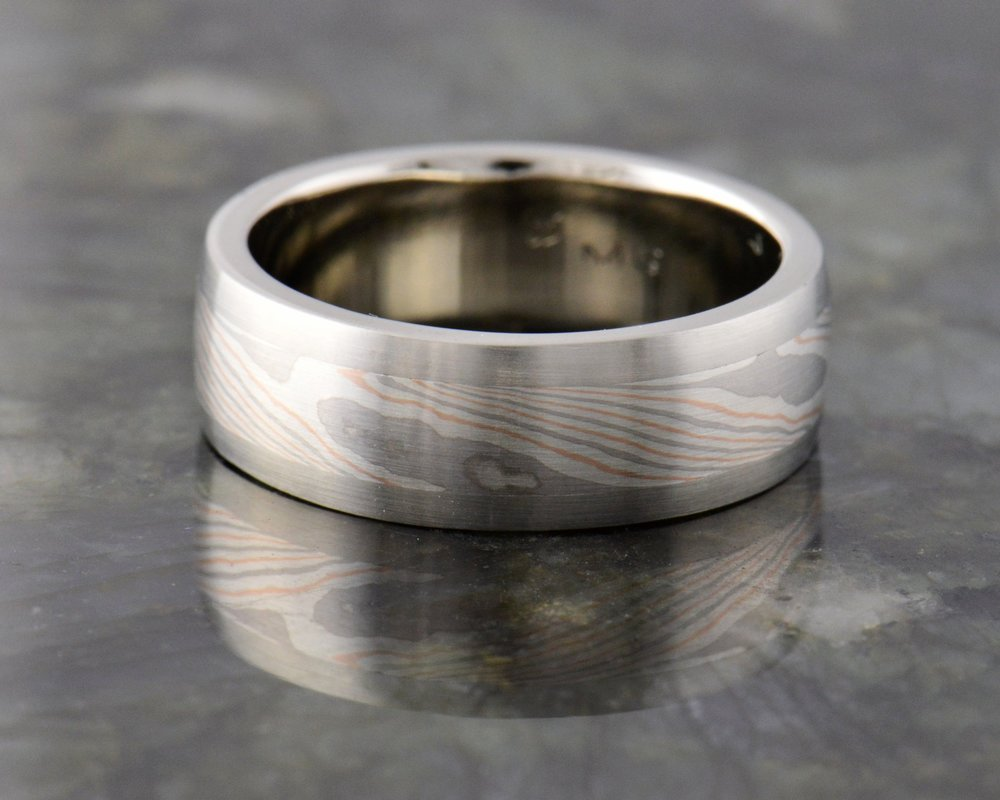 Mokume inlay - Taking our hand forged designs of bonded precious metals, inlaying it into solid bands of any metal. Have a look at our Mokume  possibities .