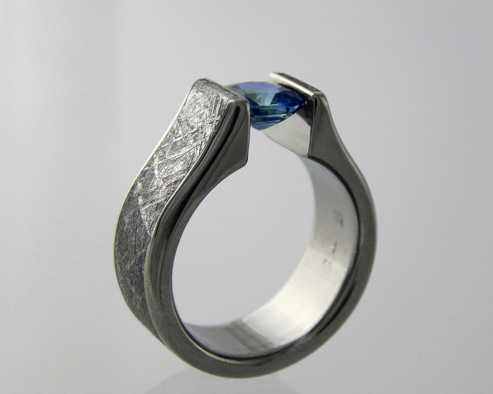 Tension settings - 3D printed titanium rings built to the exact needs of the gem it's holding securely using the memory of the metal to keep it in place. This one is built with a gibbeon meteorite inlay. We recommend moissanite or created sapphire for daily wear.