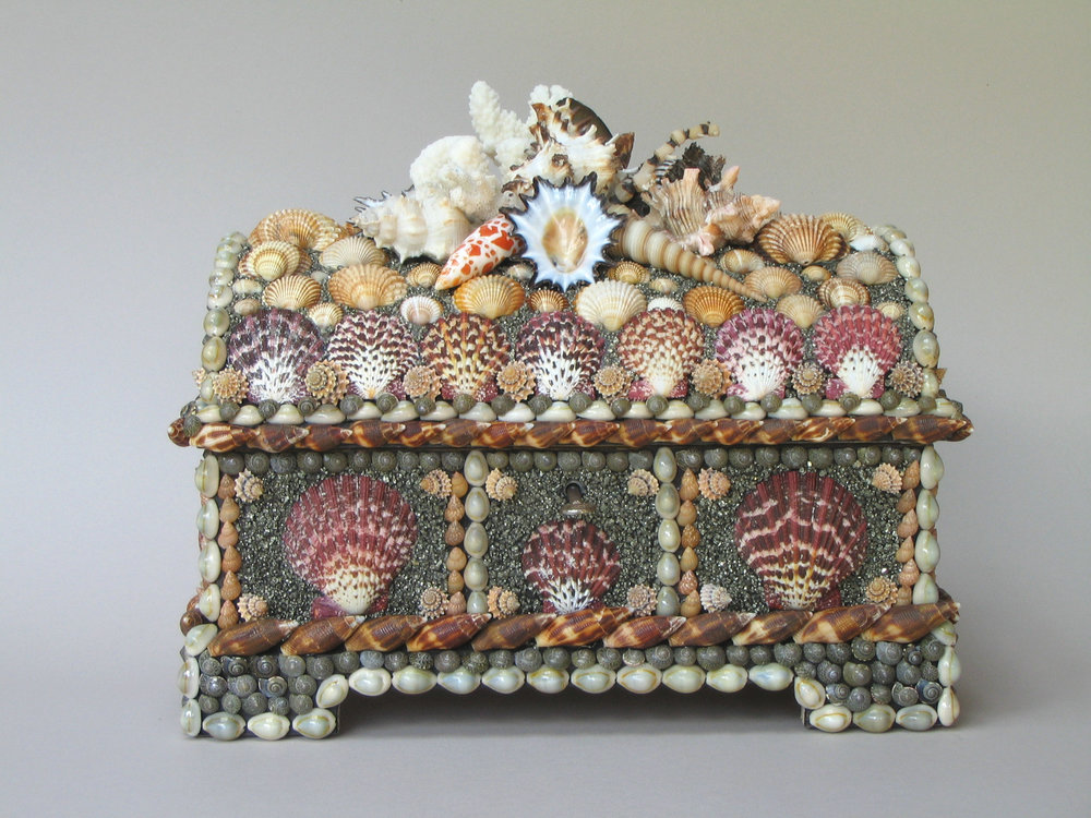 An unusual casket decorated with red cloak scallop shells mounted on a golden background. The lid is crowned with a cluster of mixed shells and corals. 11 '' ×13 '' ×9 ''