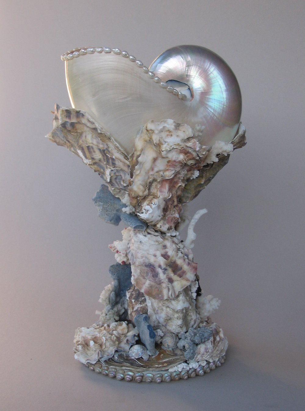 A mother-of-pearl nautilus shell held on a stand of overlapping oyster shells with antique white coral, the lip of the cup is edged with river pearls. 11 ''