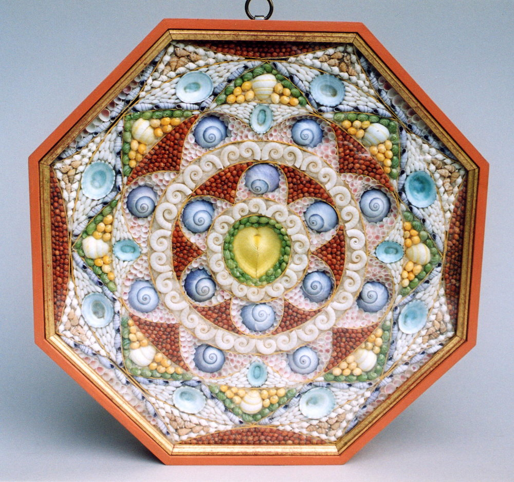 A very intricate valentine of geometric patchwork design made up of sixty-two compartments. The half circles filled with pink blossom and purple snail shells radiate outwards forming a star pattern of green and yellow shells. 12 ''