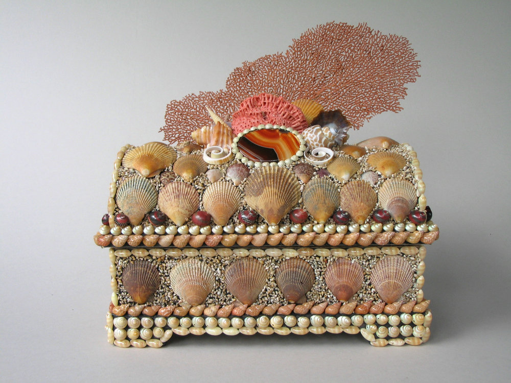 Casket crowned with magnificent fan coral. The agate cabochon flanked by cut spirals and reddish-brown shells on an unusual background of miniature sand-coloured shells. 9 1/2 '' ×8 '' ×5 ''