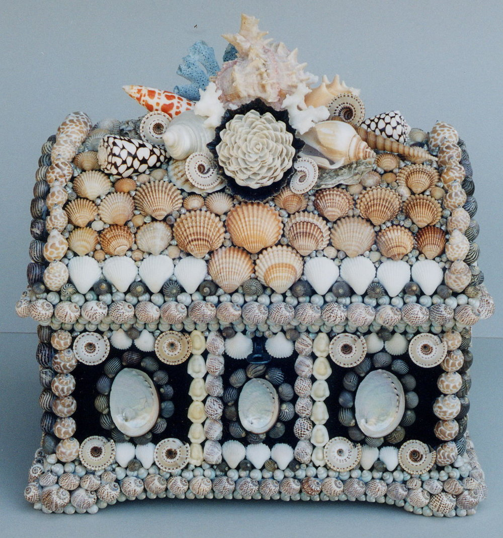 A large casket, the domed lid profusely encrusted with a pink-mouth murex, orange mitre, leopardcones, sundials, blue and white coral fragments, a large South African limpet with a rose made from a hundred miniature cup shells. 9 '' ×12 '' ×8 ''