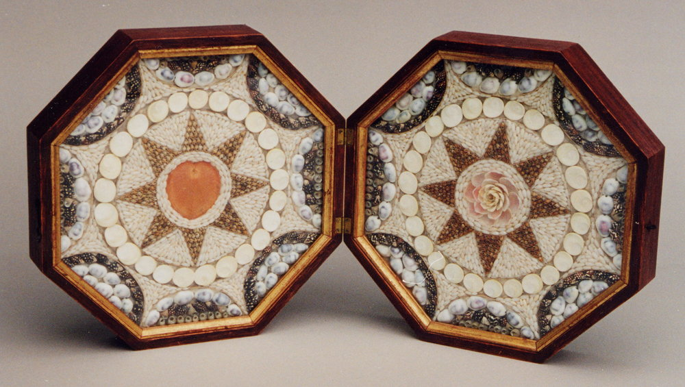 A double valentine with star  designs surrounded by rice grain shells; the left with a heart centre, the right with a rose. Brass clasp and hand marbled paper backing. Each face 9 ''