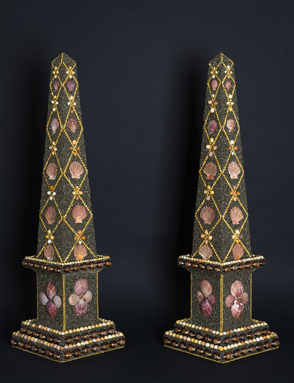 A glittering  pair of obelisks with lattice panel designs. Yellow seed shells, scallops and snakehead cowries arranged on a background of crushed mineral. 82 x 23 x 23 cm