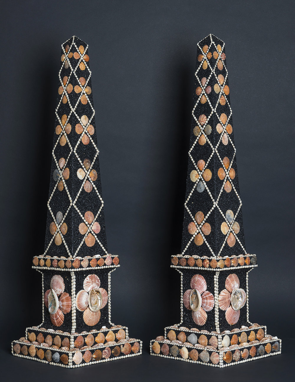 A dramatic pair of obelisks embellished with abalones and scallop shells set on a background of crushed anthracite. 82 x 23 x 23 cm