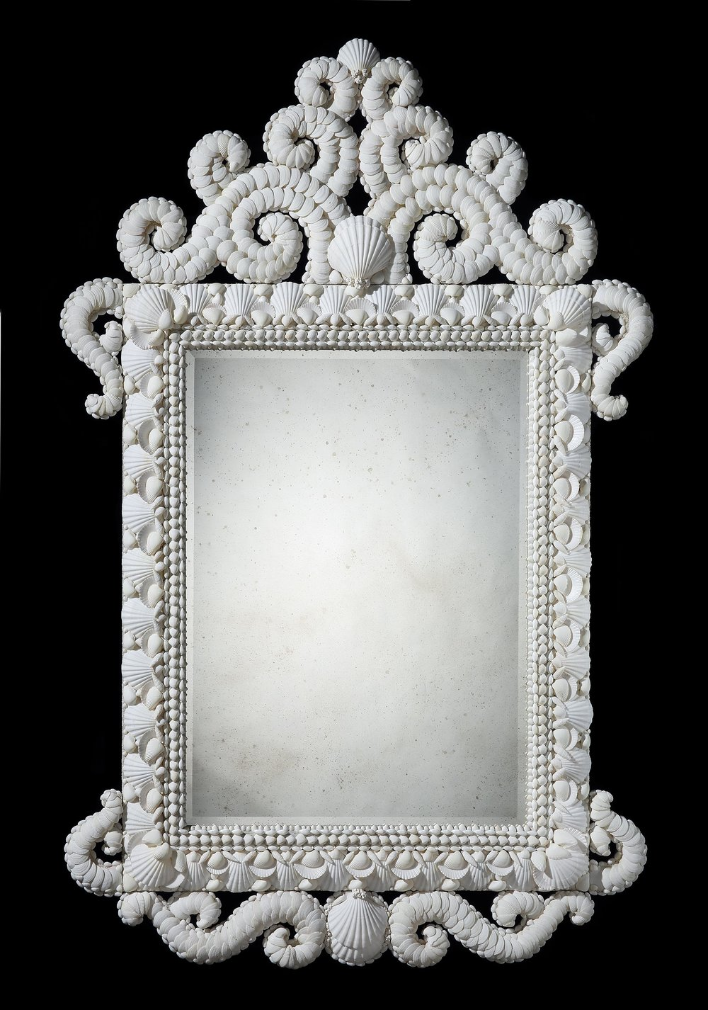 Large White Shell Mirror  A magnificent white shell mirror with ascending scroll pediment, matching sides and apron. A vast selection of carefully chosen white shells have been used to embellish this ornate looking glass.Mirror plate hand distressed and with bevel edge.  200cm x 130cm