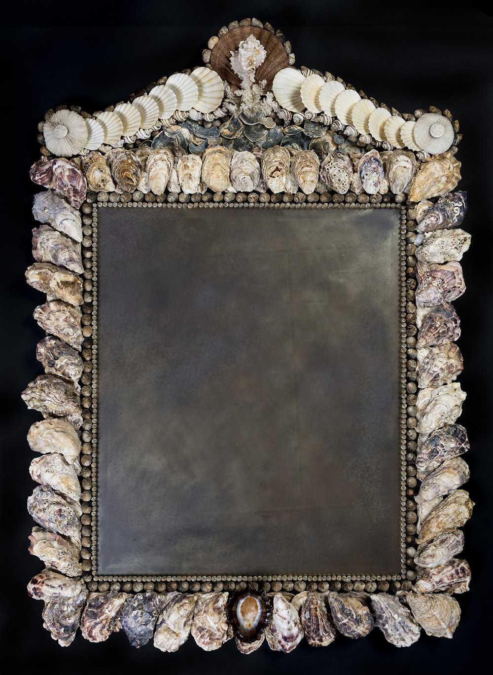 Oyster Shell Looking Glass   A rectangular looking glass with native winkle and oyster shell surround.  The pediment with scallop shell finial surmounted by a single murex and flanked by broken scrolls of white fan shells. A black South African limpet pendant to the base.  97cm x 70cm