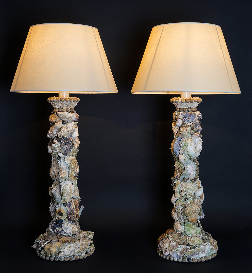 A pair of grotto lamps decorated with English native shells including oysters, winkles and whelks. Each base supports a branch of antique weathered coral. 70cm x 26cm approx