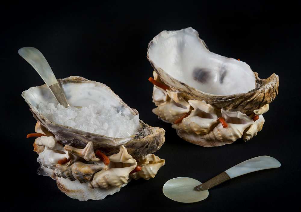 A Pair of Oyster Salts   A pair of oyster shell salts with interlocking pelican shells and fragments of antique, red, polished corals around the base. Two miniature mother-of-pearl spoons included. 10cm x 5cm