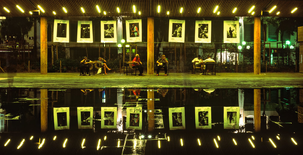 Coulée Verte - People sitting under posters of Jazz legends in the evening.