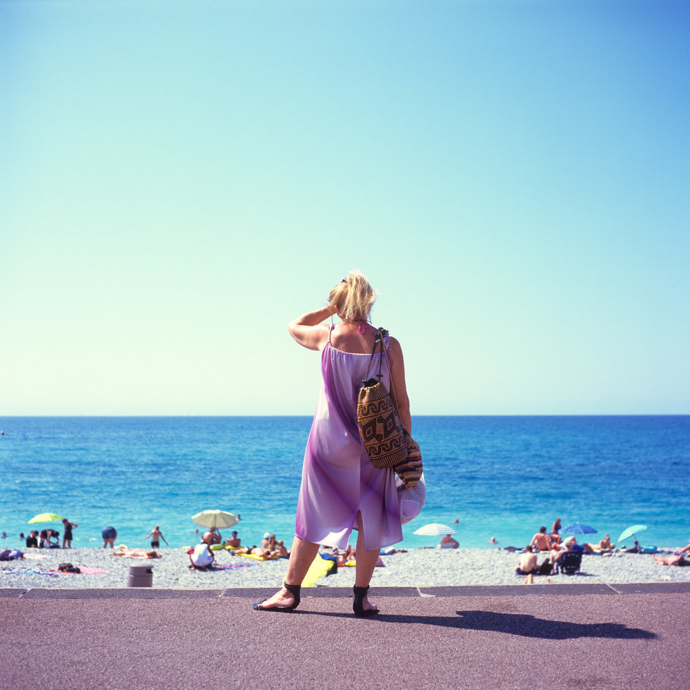 Madame lilas - A woman in purple dress looks at the ocean.
