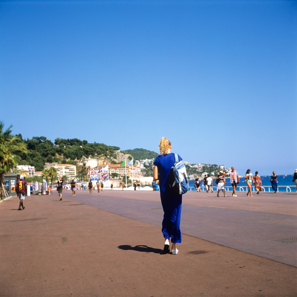 Madame bleue - A woman in blue dress walks along the promenades des anglais.