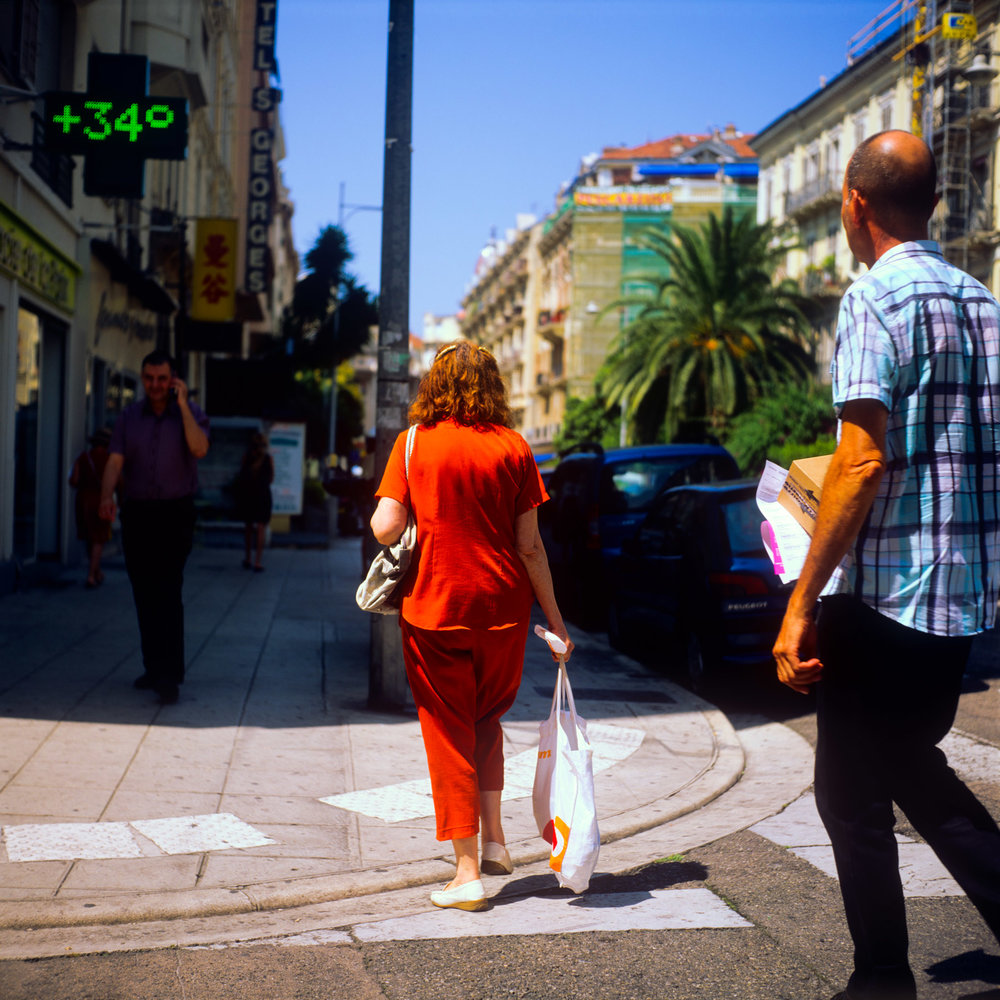 Madame rouge - A woman in red dress crosses the street.