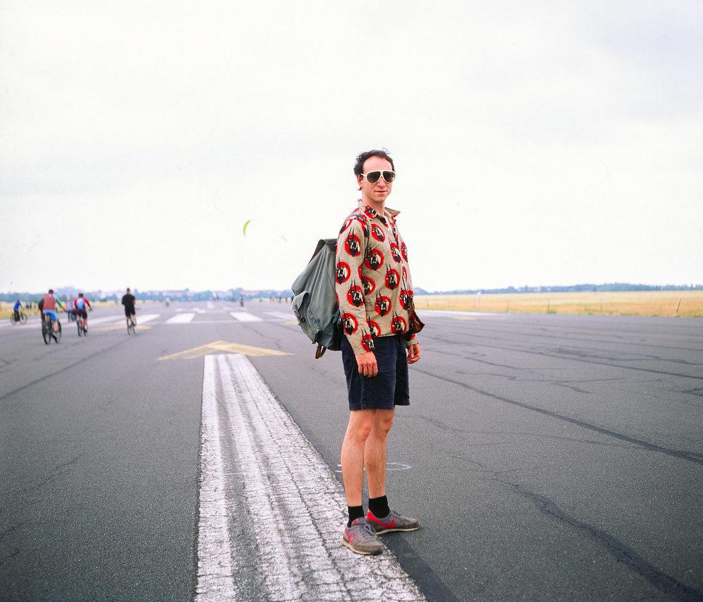 George trägt Nike Schuhe, vintage Sonnenbrille und Kordshorts auf dem Berliner Tempelhofer Feld.