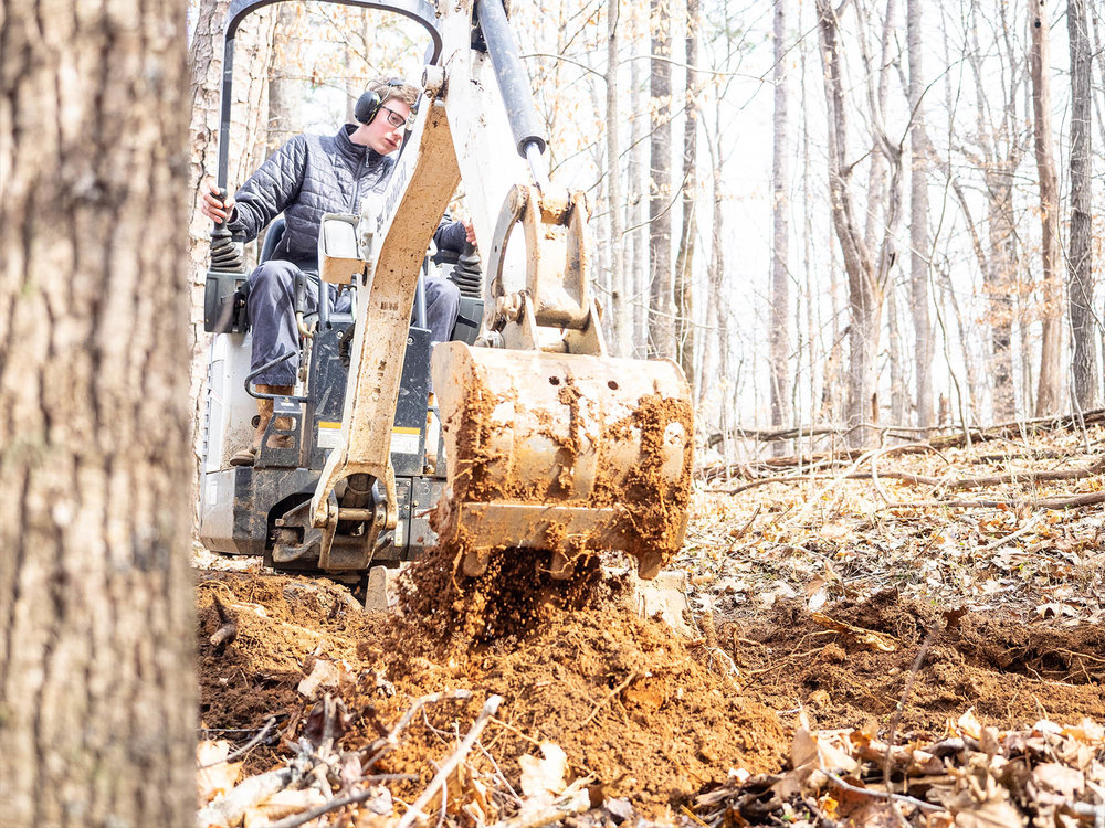 customImage  Operating the mini excavator one mile into his new trail.  SAM ROACH