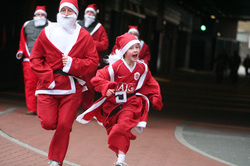 Parent and child dressed as Santas, running