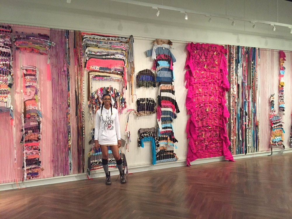 Whitney in front of wall weaving.jpg