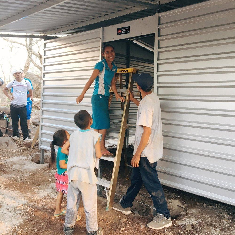 Naomi, Elias, Jefferson and Helen receiving their home.