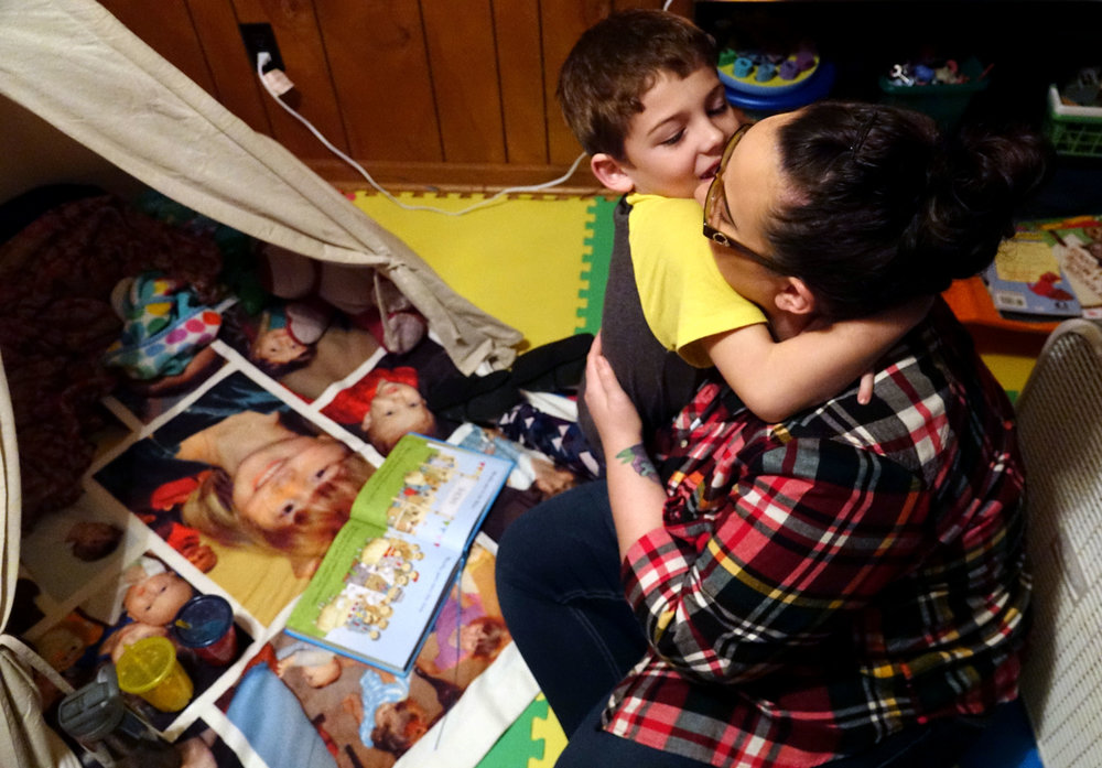 """Jaxon Henderson, 7, hugs his mom, Jamie Henderson, while they read together before bedtime in Richland, Missouri. Jaxon was diagnosed with autism when he was 2 years old. """"You kind of grieve for a little bit because, you know, you wanted your baby to be typical and grow up normal, and it's not going to happen for him,"""" Jamie said. Credit: Kyra Haas / KBIA"""