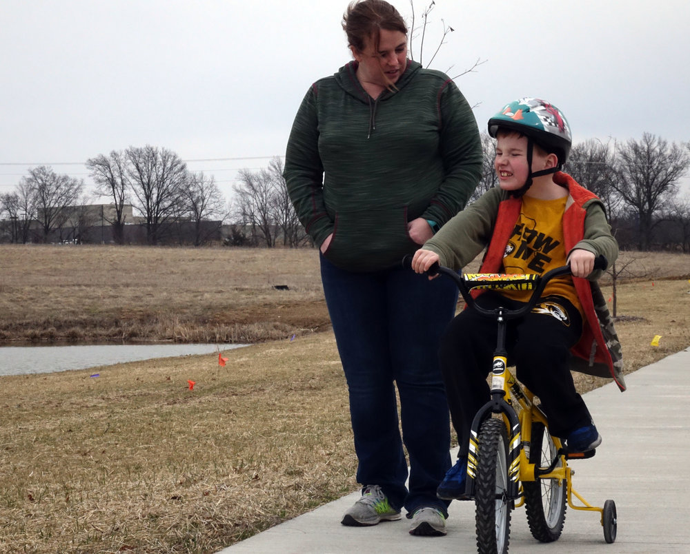 """Tara Arnett watches her son, Logan, 8, ride his bike near their home in Columbia, Missouri. Logan was diagnosed with autism when he was 2 years old. """"He was the best baby,"""" Arnett said. """"He was super easy, super well-behaved. He slept. He did everything; we thought we were awesome parents. He was probably too well-behaved for his age, in hindsight … He didn't need us. He never cried for us."""" Credit: Kyra Haas / KBIA"""