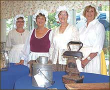 Historical Society Colonial Ladies describe a variety of artifacts. From left, Izzy Gilman, Linda Tetrault, Norma Rogers and Caroline Rowe.