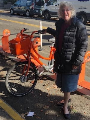 Photo of Kaaren Londahl standing next to an orange biketown bicycle in northeast Portland.