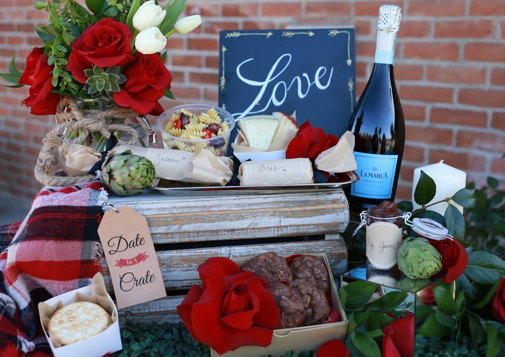 Includes; Fresh professionally arranged flowers in a unique glass vase by TRENDEE, fine pre-sliced cheese (for 2), brie soft cheese roll (for 2), mini fine salami loaf (for 2), stack of specialty crackers, handmade fig jam, deli size of spiral Mediterranean pasta (for 2), triple chocolate gourmet cookies (set of 4), a romantic candle and bow, La Marca sparkling white wine, and wooden crate to hide your special treats on your adventure.  Bonus gift included:  Valentine themed scarf (for her).