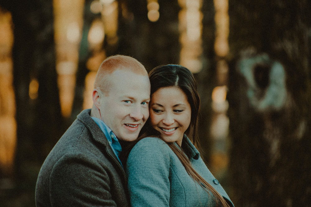 A couple get close and smiles in front of trees with glowing sun.