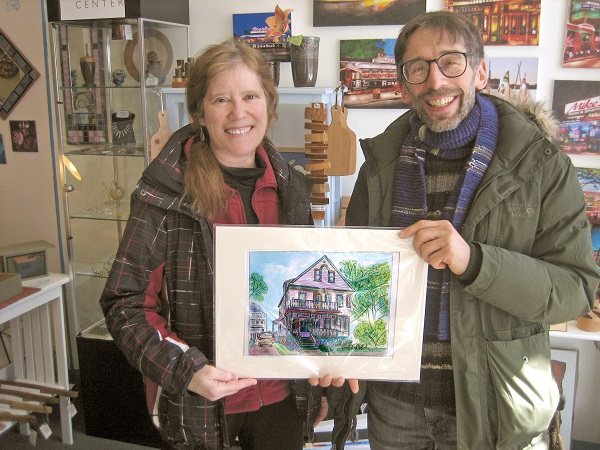 Tamara Major of Medford gives custom watercolor she painted of his house to Macy Coffey of Somerville.