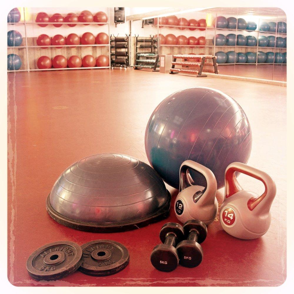 Fitnessmaterialen: kettlebells, dumbbells, een fitbal, een Bosu en schijven voor een barbell.