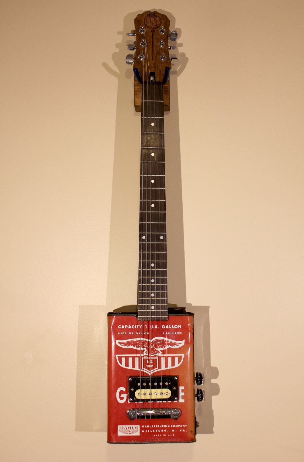 Weeping Poppy   $400 vintage gasoline can, guitar neck, humbucker, bridge, potentiometers, woodstain, wood seal, pyrography