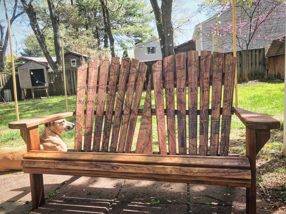 "Bench designed for Discover Purcellville titled ""Woodgrove"" — Sold at auction for $1650   This bench was created for the Discover Purcellville arts program for the summer of 2018. It features a woodburned map of the Western Loudoun towns of Round Hill, Purcellville, and Woodgrove, a small settlement originally located just north of Round Hill. The bench sat in front of Catoctin Creek Distilling Co. in Purcellville, VA and went home with a private buyer after the auction in November."