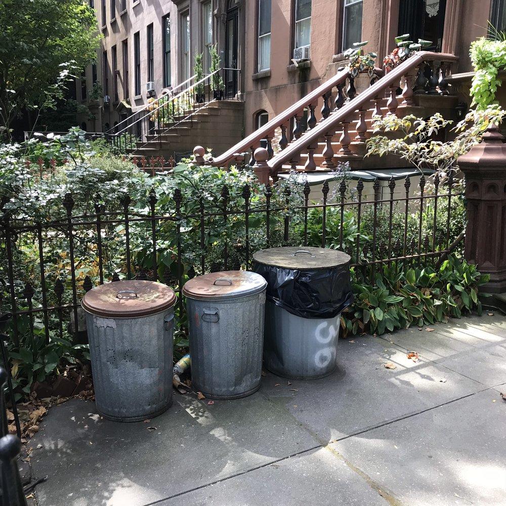 Metal trash cans in brownstone Brooklyn.