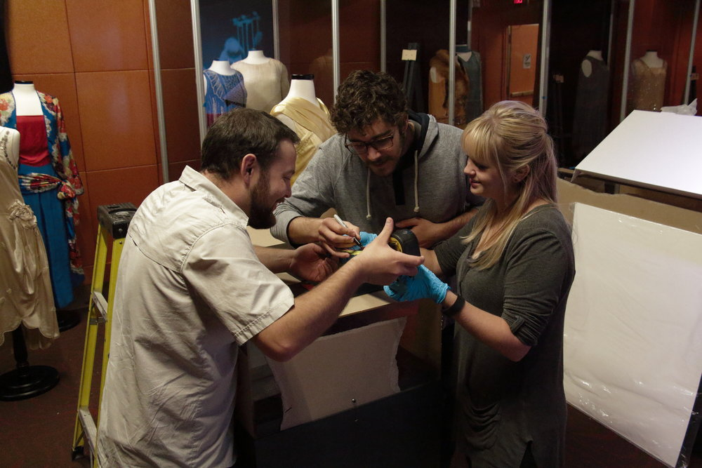 Three graduate students work on labels for the Ready to Roar exhibit inside the Mob Museum.