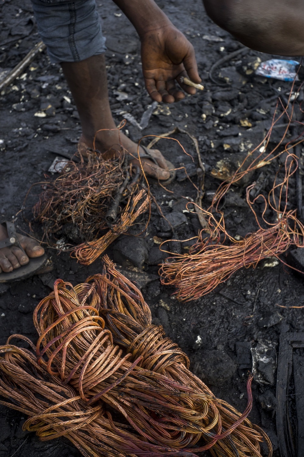 Awal sorts through bundled copper reclaimed from electronic waste. Awal cools the metal he just finished burning.