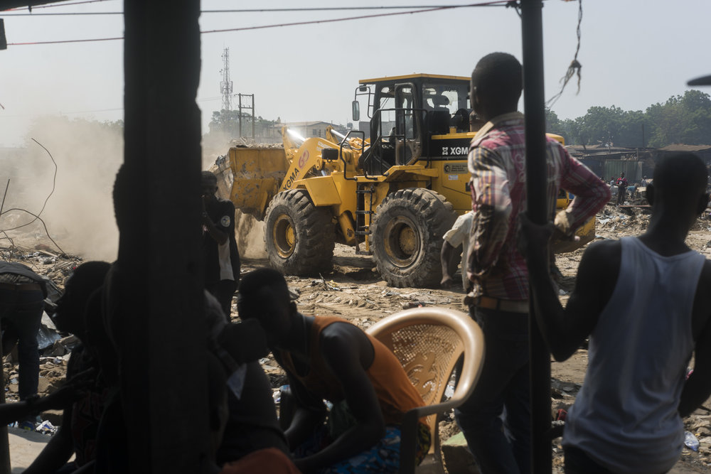On a Saturday morning in June 2015, the Accra Metropolitan Assembly (AMA) demolished the homes of over 20,000 people in Agbogbloshie to dredge the waterways and avoid the floods that affect the city every year during the rainy season. Awal and his friends watch from a distance.